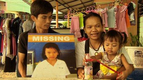 Kamol and Manee Thongchum with baby Om, and a missing persons poster to Jiji