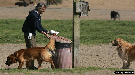 A man putting a dog poo bag in a bin