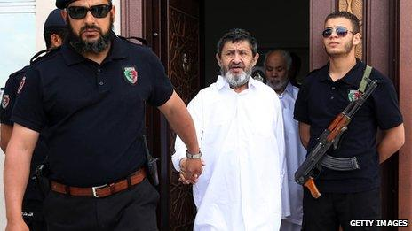 Former Libyan congress president Mohamed Balgassem al-Zway (C-back) and former Libyan foreign affairs minister Abdelati Obeidi (C) are escorted by police following a hearing in their trial on May 6, 2013 in the capital Tripoli.