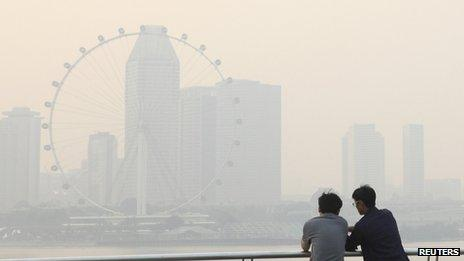 Men watch the sun set in the hazy skyline of the Singapore Flyer on 18 June 2013