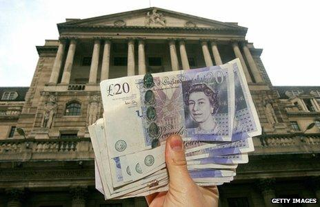 Hand holding up pounds in front of the Bank of England