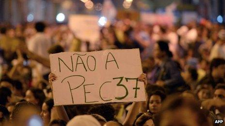 """A protester holds up a banner saying: """"No to PEC 37"""" at a demonstration in Niteroi, Rio de Janeiro State (25 June 2013)"""