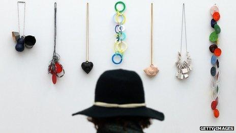 A visitor looks at jewellery on display at the Collect art fair at Saatchi Gallery on May 9, 2013 in London, England