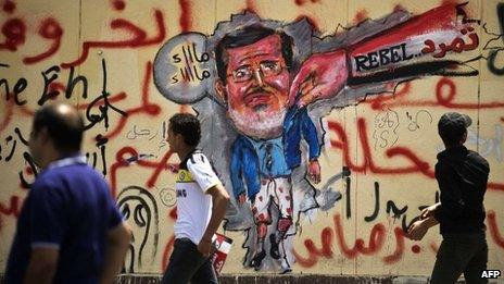 Protesters walk past graffiti depicting Mohammed Morsi near the presidential palace in Cairo (1 July 2013)