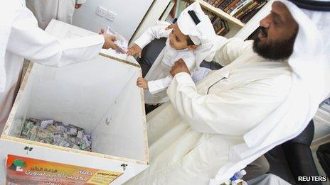 Kuwaiti former MP al-Sawagh helps a Kuwaiti child toss a donation into a wooden box designated to support the Syrian Opposition (27 June 2013)