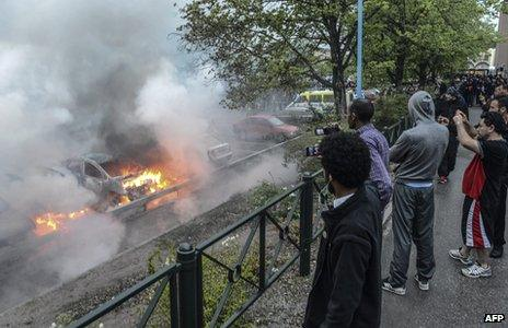 Bystanders take photos of a row of burning cars in the Stockholm suburb of Rinkeby (May 23, 2013)