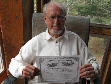 Pastor Roger Lynn holds up the marriage certificate of Michael McConnell and Jack Baker