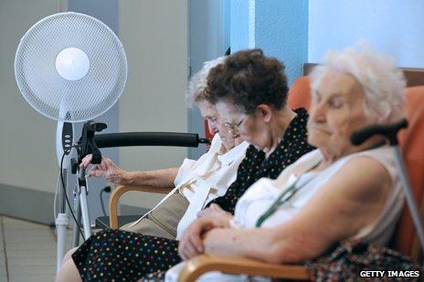 Old women sitting in front of fan