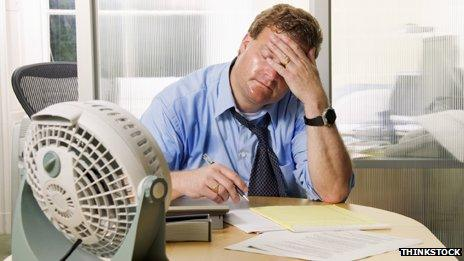 A man sweating while working in an office with a small fan