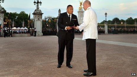 The Queen's senior page Philip Rhodes is given the document