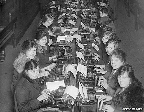 Female workers sit in two long rows in front of typewriters