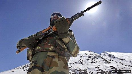 An Indian soldier standing guard on a mountainous road in the border area