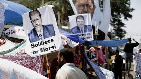 A supporter of Egypt's Islamist President Mohammed Morsi in front pictures of President Mohammed Morsi at Nasr City