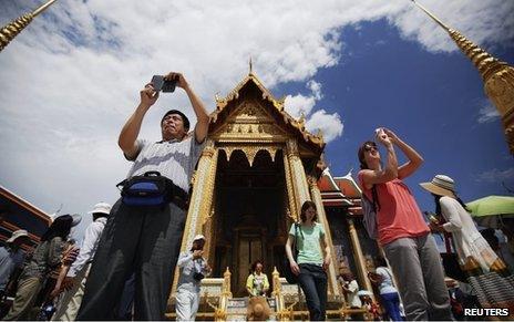 Tourists take photos at the Grand Palace in Bangkok