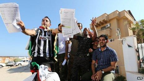 Libyan protesters display documents they have ransacked from the offices of Muslim Brotherhood-backed Party of Justice and Construction, in the Libyan capital Tripoli on 27 July, 2013