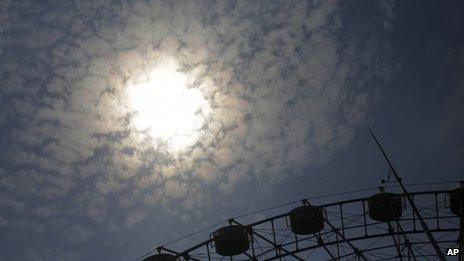 A ferris wheel is lit up by the hot summer sun in Shanghai, China, 26 July 2013
