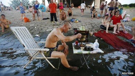 A man sitting on a beach chair in his swimming trunks takes his meal at a small table partially dipped into the Hanjiang river to escape the summer heat, as other swimmers look on under a bridge in Wuhan, Hubei province, 28 July 2013