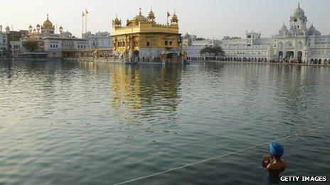 A Sikh man takes a dip in the water beside the Golden Temple