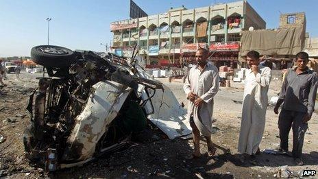 A picture taken on July 29, 2013 shows Iraqis inspecting the site of a car bomb explosion in the impoverished district of Sadr City in Baghdad.