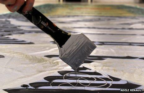 Close-up of paint dripping from a brush and forming a decorative element similar to a Celtic knot