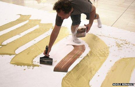 Close-up of Niels Shoe Meulman painting huge golden letters