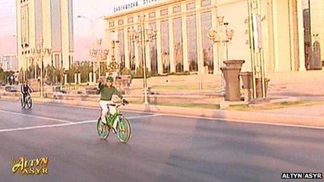 Gurbanguly Berdimuhamedov raises an arm in victory