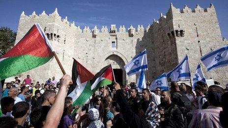 In this 8 May 2013 file photo, Israelis and Palestinians wave flags outside Damascus Gate in Jerusalem's old city