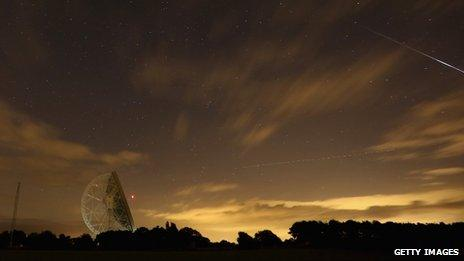 Perseid meteor streaks across the sky past the light trail of an aircraft over the Lovell Radio Telescope at Jodrell Bank in Holmes Chapel