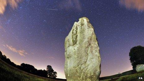 """A meteor is seen during the Perseids meteor shower over the one of the stones of the Avebury""""s Neolithic henge monument in Wiltshire"""