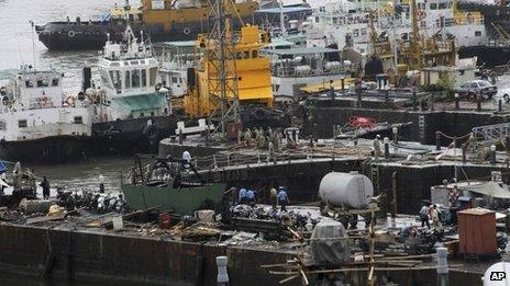 Ships are moored at a naval dockyard where a submarine caught fire and sank after an explosion early Wednesday in Mumbai, India, Wednesday, Aug. 14, 2013