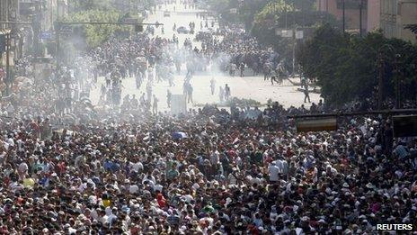 Supporters of ousted Egyptian President Mohammed Morsi run away from tear gas during clashes in Cairo 16 August, 2013.