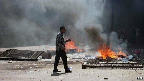 An Egyptian Muslim Brotherhood supporter walks near fires in Cairo's Ramses square on 16 August, 2013.