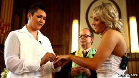 Natasha Vitali (L) and Melissa Ray (R) exchange rings with marriage celebrant Rev Matt Tittle at the Auckland Unitary Church on August 19, 2013 in Auckland, New Zealand