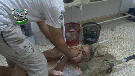 Alleged victim of chemical weapons attack covers his face as he is given an oxygen mask to help him breathe on 21 August 2013