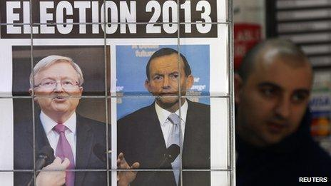 A man walks behind an advertisement for a newspaper with pictures of Australian Prime Minister Kevin Rudd (L) and opposition leader Tony Abbott in central Sydney, 5 August 2013