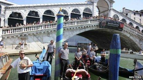 Gondoliers pay their respects, as people line the bridge, in front of the place near Rialto bridge where a German tourist was killed in Venice taken on 18 August 2013