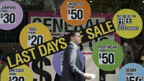 A man walks in front of a shop displaying items on sale in the central business district of Sydney on 5 June 2013