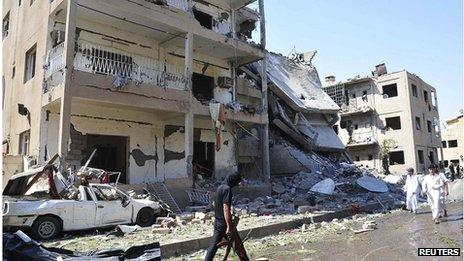 A man holds a weapon as he walks past damaged buildings at a site hit by what activists say was a car bomb in Raqqa province, eastern Syria August 29, 2013