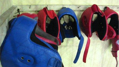 Protective headgear hangs from a wall in La Finca gym