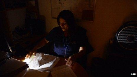 A woman works during a blackout in Caracas on 3 September, 2013.