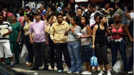 Caracas residents wait for a bus during a power cut on 3 September 2013