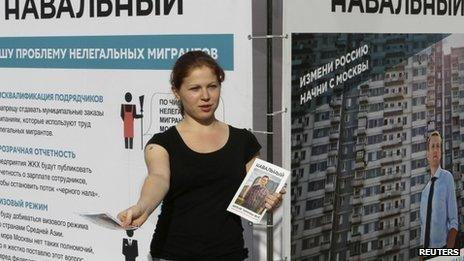 A campaign staffer of opposition leader Alexei Navalny distributes leaflets near a campaign booth on a street in Moscow on 3 September 2013
