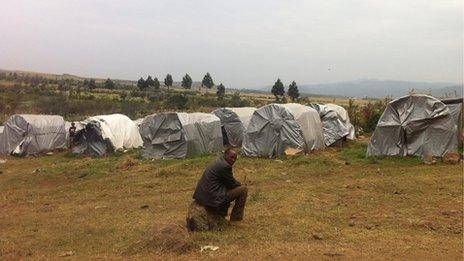 Man in front of tents in Kenyan refugee camp