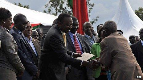 Kenya's President, Uhuru Kenyatta, and his deputy, William Ruto, hand out cheques on September 7, 2013 at Eldoret in Kenya's North-Rift
