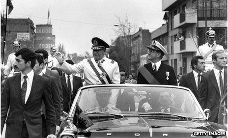 General Augusto Pinochet (l) waves from the motorcade 11 September 1973 in Santiago, shortly after his coup that killed President Allende