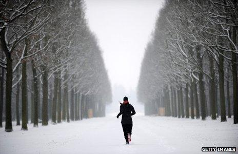 Jogger runs through snowy forest