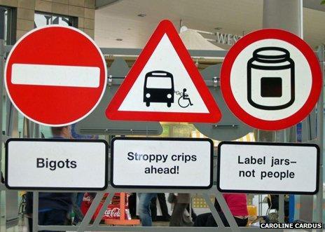 "Signs reading ""bigot"", ""stroppy crips"", ""label jars"""