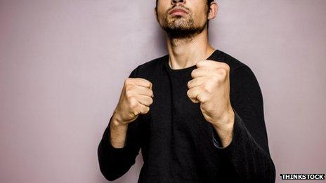 Unidentified man in black sweater with fists raised