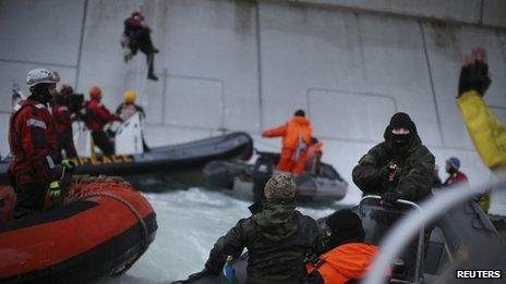 Greenpeace image it says shows a Russian coastguard pointing a gun at activist