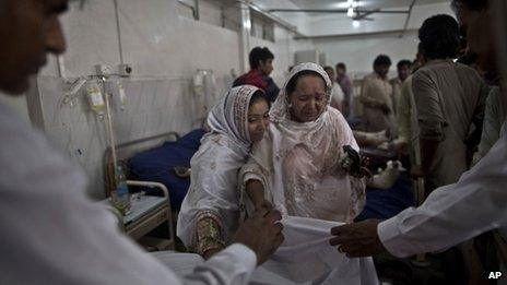 A Pakistani woman grieves as doctors cover the body of her mother, killed in a suicide attack on a church in Peshawar, Pakistan, 22 September, 2013